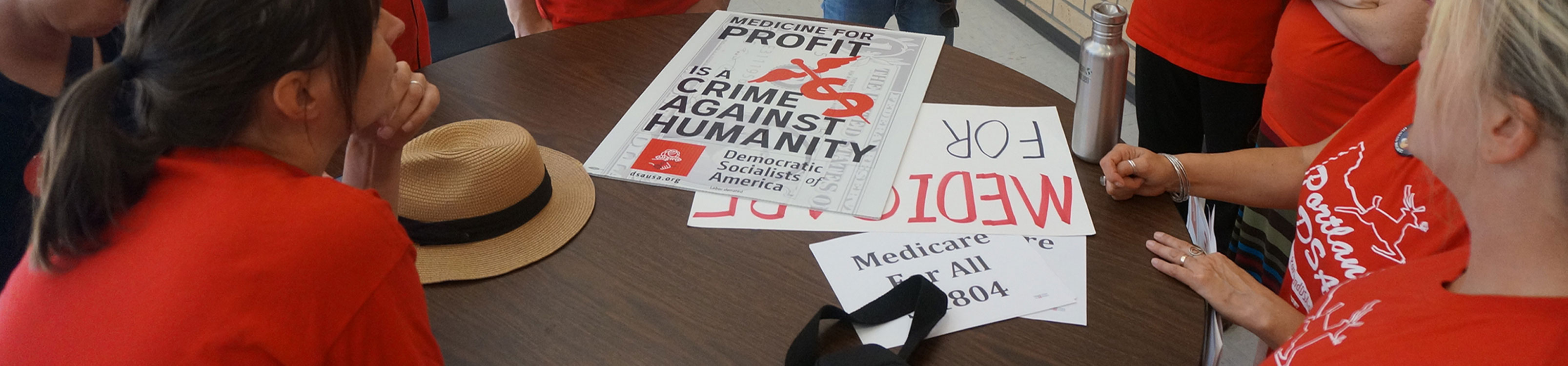 Medicare for All posters on a table, while a meeting of activists occurs. All wearing Portland DSA shirts.